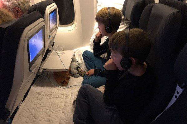 My boys enjoying the entertainment before settling down to sleep on the Air NZ Skycouch